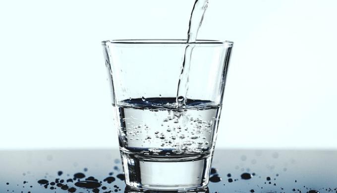 グラスに水を注いでいる画像